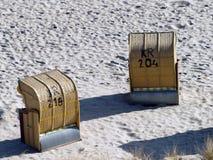 Roofed rieten ligstoelen op het strand Stock Foto
