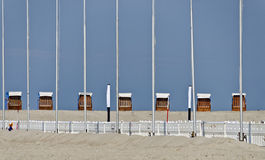 Roofed wicker beach chairs and flagpoles Royalty Free Stock Photography