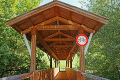 Roofed wooden bridge. Only for pedestrians and a prohibition sign for bicycles Royalty Free Stock Photography