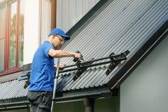 Roofer устанавливая предохранитель снега на крышу металла стоковые фото