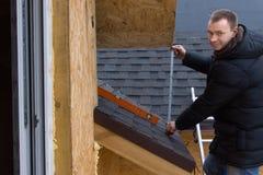 Roofer amigável que toma uma medida fotografia de stock