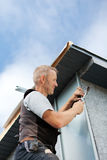 Roofer assembling a metal piece into the dormer Stock Photography