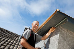 Roofer assembling parts of the dormer. Rooftop edge Stock Photography