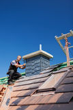 Roofer assembling tiles on a chimney Stock Photo