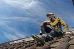 Roofer barbuto che riposa sopra un giorno soleggiato del tetto Immagine Stock