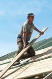 Roofer bei der Arbeit über Gebäude Stockbilder