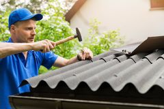 Roofer installing bitumen roof sheets Stock Photos