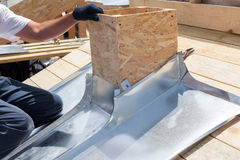 Roofer builder worker attach metal sheet to the chimney. Stock Photography