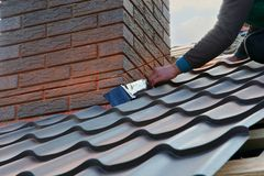 Roofer builder worker attach metal sheet to the chimney. Unfinished roof construction Stock Image