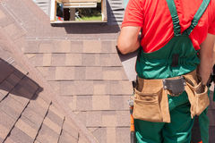 Roofer builder worker with bag of tools installing roofing shingles. Royalty Free Stock Photo