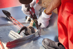 Roofer builder worker finishing folding a metal sheet using metal shears. Stock Photo