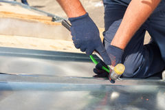 Roofer builder worker finishing folding a metal sheet using rubber mallet Stock Photos