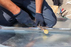 Roofer builder worker finishing folding a metal sheet using rubber mallet. Stock Image