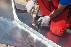 Roofer builder worker finishing folding a metal sheet using rubber mallet. Royalty Free Stock Images