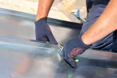 Roofer builder worker finishing folding a metal sheet using special pliers with a large flat grip. Stock Photos