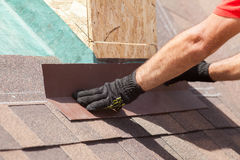 Roofer builder worker installing shingles on a new wooden roof with skylight. Royalty Free Stock Images