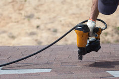 Roofer builder worker with nailgun installing Asphalt Shingles or Bitumen Tiles on a new house under construction. Roofer builder worker with nailgun installing stock images