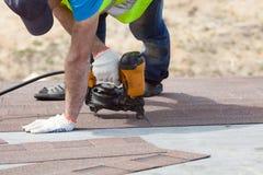 Roofer builder worker with nailgun installing Asphalt Shingles or Bitumen Tiles on a new house under construction. Stock Photo