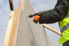 Roofer builder worker use drill to make a hole in structural Insulated Panel. Stock Image