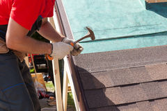 Roofer builder worker use a hammer for installing roofing shingles. Royalty Free Stock Photos