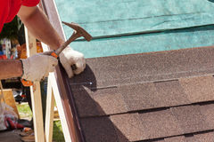 Roofer builder worker use a hammer for installing roofing shingles. royalty free stock photo