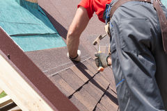 Roofer builder worker use a hammer for installing roofing shingles. Stock Images