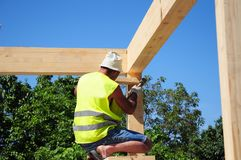 Roofer building house roof wooden trusses. Contractor with Hammer  Roofing Construction. Roofer Construction. Roofer building house roof wooden trusses Stock Photo