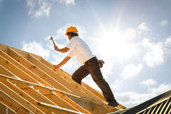 Roofer carpenter working on roof on construction site. Outdoors with sunflare and blue sky and copy space Royalty Free Stock Images