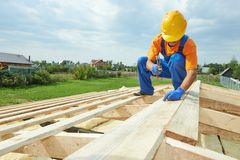 Roofer carpenter works on roof Stock Photos