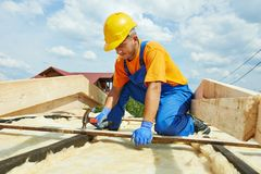 Roofer carpenter works on roof Royalty Free Stock Images