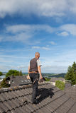 Roofer carrying tools on the rooftop Royalty Free Stock Photography