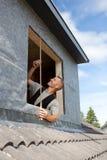 Roofer che appronta le misure per una nuova finestra immagine stock