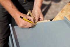 Roofer che per mezzo di una matita e righello per fare le marcature Fotografia Stock