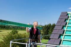 Roofer che porta un fascio di legno sul tetto Fotografie Stock Libere da Diritti