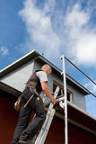 Roofer climbing a ladder into the scaffolding Stock Photo