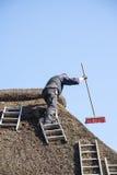 Roofer con le scale su un tetto ricoperto di paglia per rimuovere muschio e sporcizia w immagine stock libera da diritti
