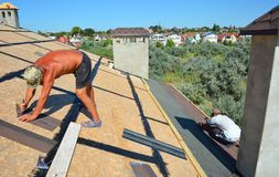 Roofer contractors laying and installing asphalt shingles. Roof asphalt shingles installation with two roofers. Roofing. Construction with roof tiles, asphalt royalty free stock image