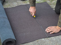 Roofer cutting roll roofing felt or bitumen during waterproofing works. Stock Photography