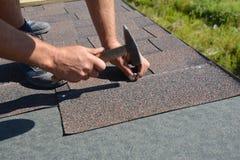 Roofer, der Asphaltschindeln auf Hausbau-Dachecke mit Hammer und Nägeln installiert Überdachung des Baus mit Asphalt stockfotografie