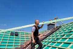 Roofer, der das Dach mit einem Strahl klettert Stockfotografie