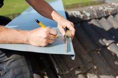 Roofer, der eine Blechtafel misst und markiert Lizenzfreie Stockfotografie