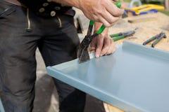 Roofer, der eine Blechtafel unter Verwendung der speziellen Zangen faltet Stockfotos