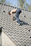 Roofer, der an einem Dach arbeitet Lizenzfreie Stockbilder