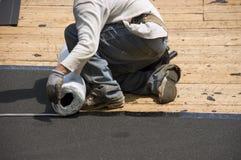 Roofer, der Eis-Schild-Teer-Papier-Schindeln niederlegt stockfoto