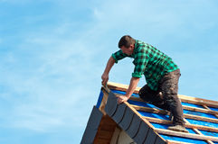 Roofer, der Schindeln anbringt Stockbild