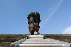 Roofer, die een ladder beklimt stock foto