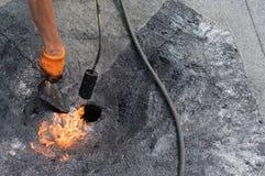 Roofer die het afvoerkanaal van het reparatiedak doen stock foto's