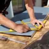 Roofer die met een gradenboog aan een metaalblad werken Royalty-vrije Stock Fotografie