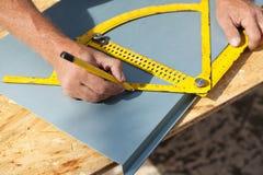 Roofer die met een gradenboog aan een metaalblad werken Stock Fotografie