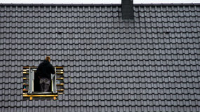 Roofer die zoldervenster installeren royalty-vrije stock fotografie